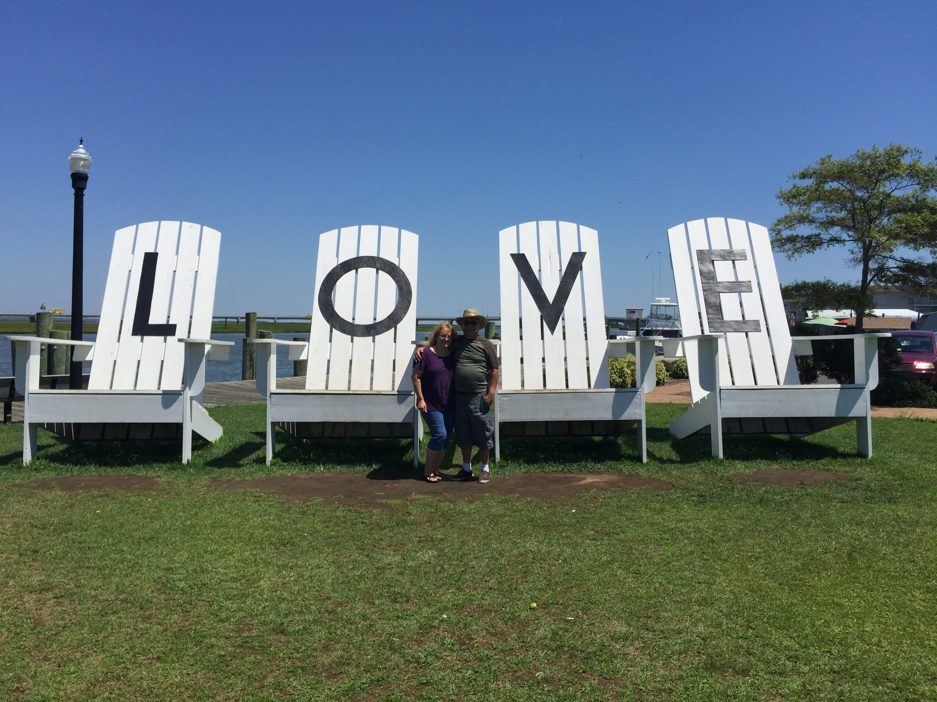 A couple staying in front of giant chairs that each have one of the letters from the word love.