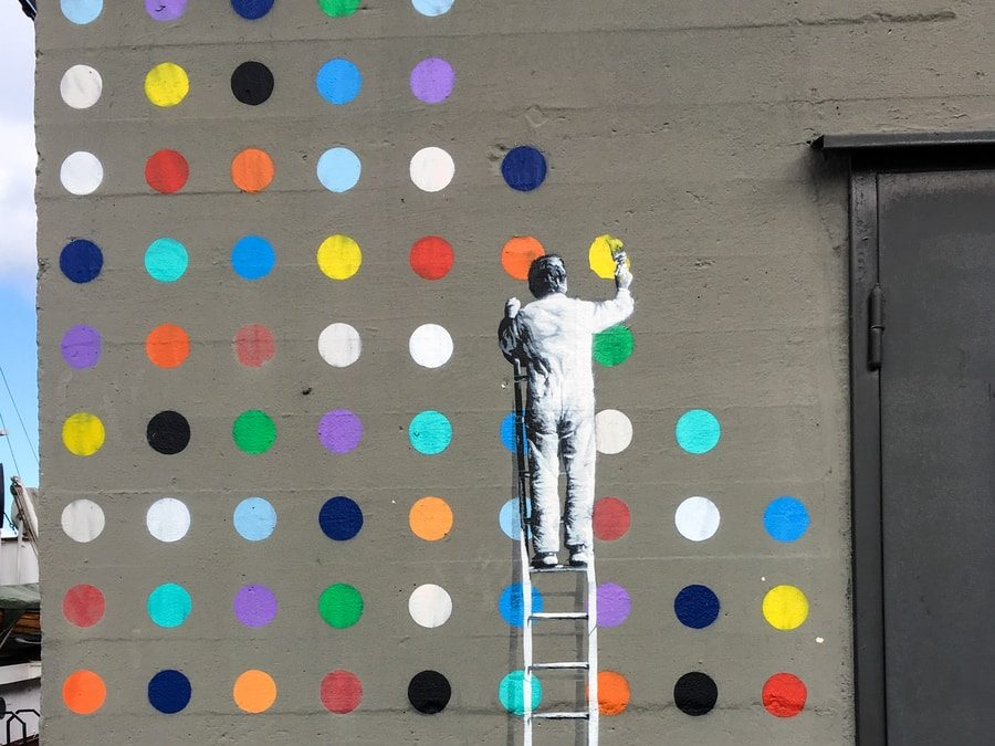 man painting on concrete wall